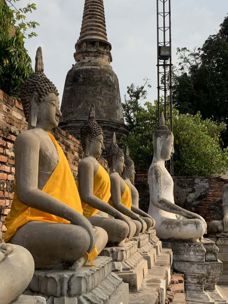 Identical row of Buddha images draped in saffron colored robes