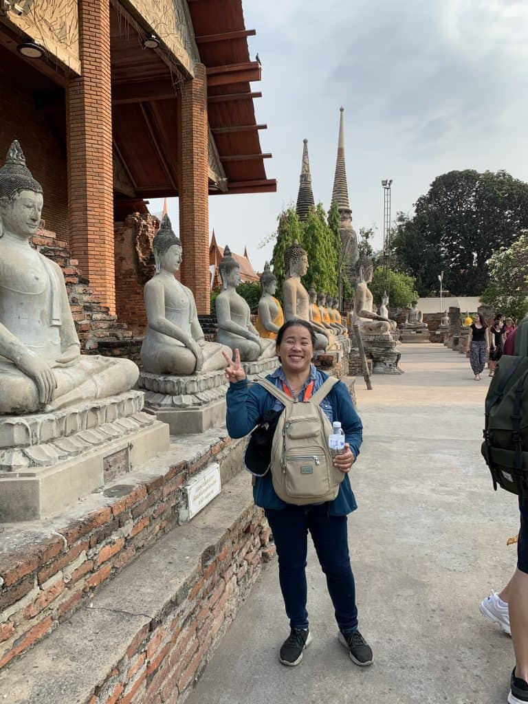 our tour guide standing in front of a row of Buddha statues